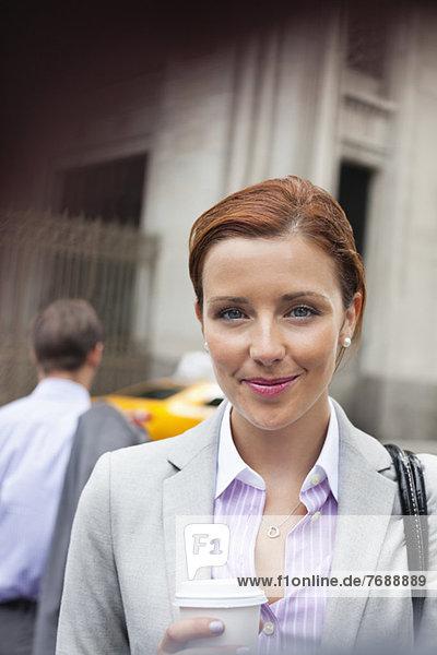 Geschäftsfrau lächelt auf der Stadtstraße