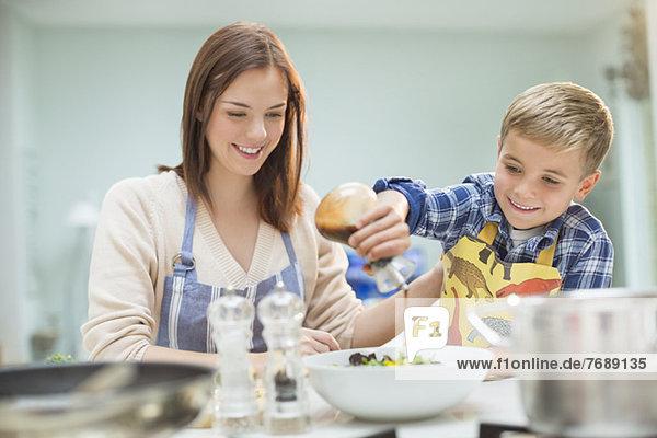 Mutter und Sohn machen Salat in der Küche