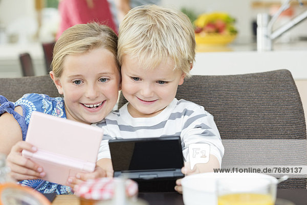 Kinder spielen Videospiele beim Frühstück