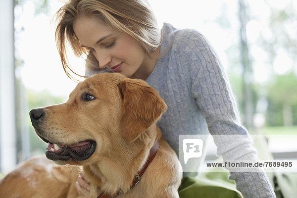 Frau entspannt sich mit Hund im Haus
