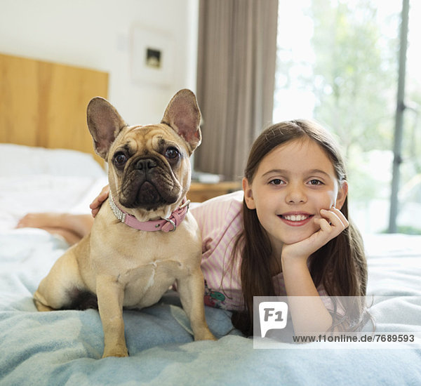 Smiling girl relaxing with dog on bed