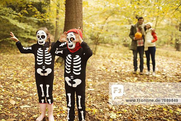 Kinder in Skelettkostümen wandern im Park