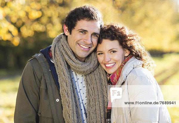 Lächelndes Paar umarmend im Park