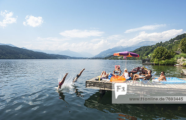 Austria  Carinthia  People sitting on pier at Millstatter See