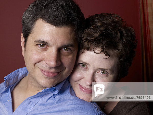 Smiling couple hugging indoors