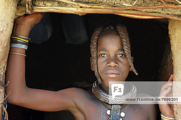 Himba girl with two braids and jewellery  portrait  Himba hut  Himba village