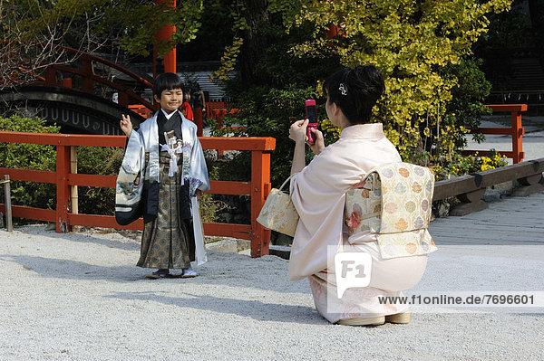 Japanischer Junge in einem dekorativen Kimono  Hakama  Hosenrock und einem Haori  Überjacke  macht Victory-Zeichen  wird von der Mutter in einem Kimono mit großer Obischleife fotografiert  beim Shichi-go-san  Sieben-fünf-drei Fest  Shimogamo Jinja  Kyoto  Japan  Ostasien