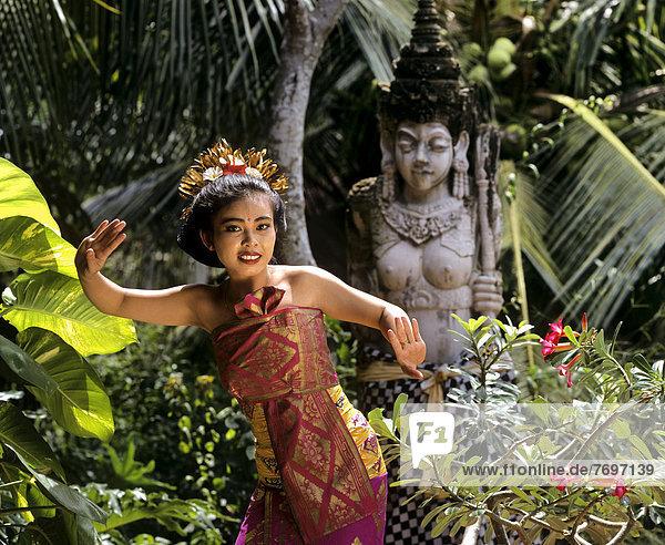 Bali-Tänzerin mit traditionellem Kostüm  vor Steinstatue
