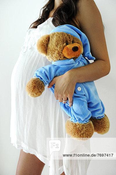 Schwangere Frau mit Schwangerschaftsbauch hält Teddybär Schwangere Frau mit Schwangerschaftsbauch hält Teddybär
