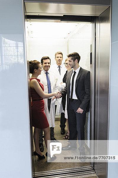 Ärzte und Geschäftsleute im Aufzug