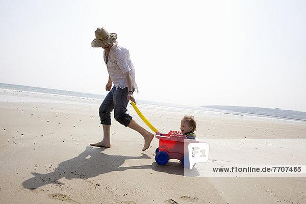 Vater mit Tochter im Wagen am Strand