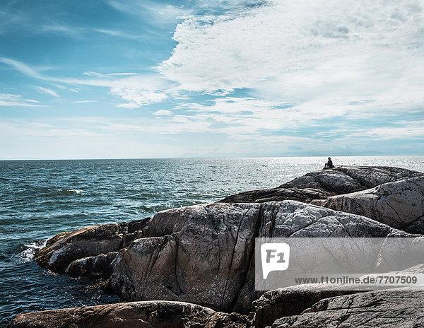Person  die auf einer Felsformation an der Küste sitzt