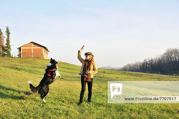 Woman playing with dog in field