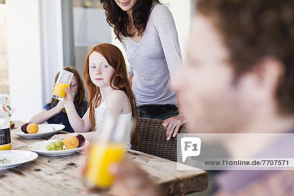 Mädchen beobachtet Vater trinken Orangensaft