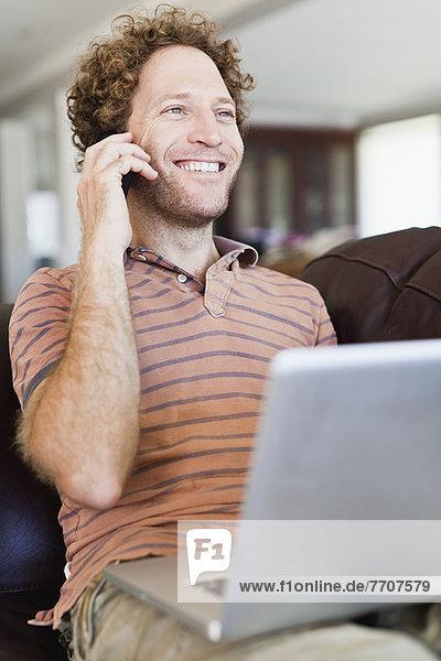 Man on laptop talking on cell phone