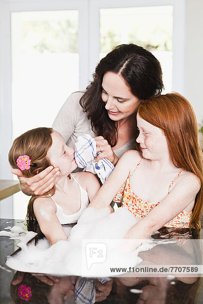 Mutter wischt das Gesicht der Töchter in der Küche ab.