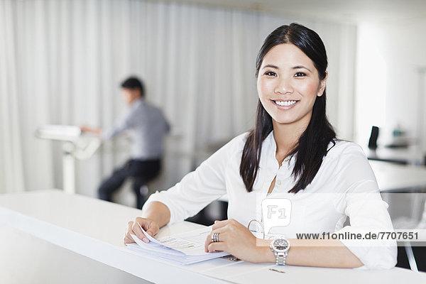 Geschäftsfrau lächelt am Schreibtisch