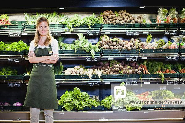 Lebensmittelhändler lächelt in der Warenabteilung