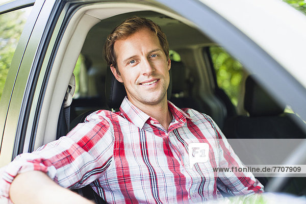 Smiling man sitting in car