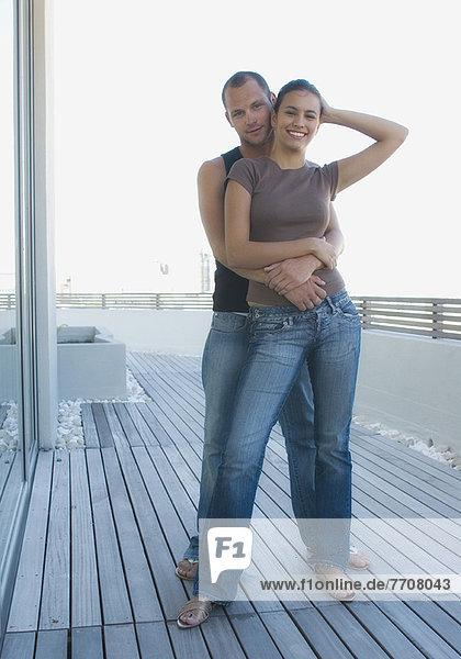 Paarumarmung auf Holzdeck