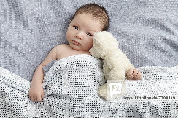Baby Junge und Teddybär im Bett liegend