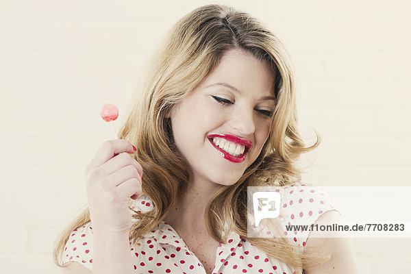 Lächelnde Frau beim Lolliessen