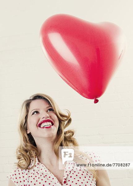 Lächelnde Frau mit herzförmigem Ballon