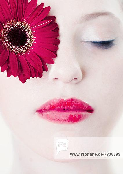 Nahaufnahme von Frauengesicht mit Blume  Mund