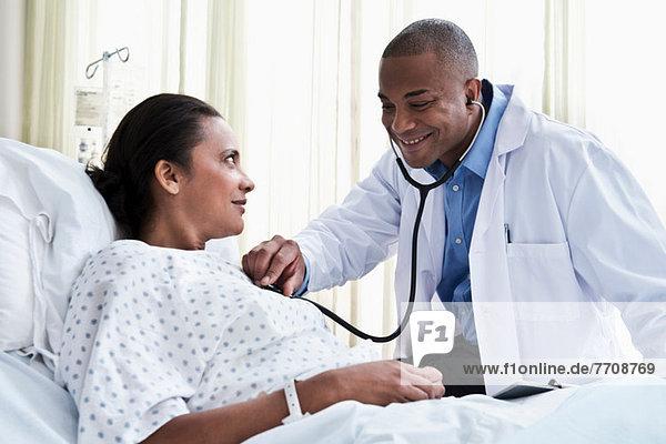 Ärztin mit Stethoskop zur Kontrolle der Patientin
