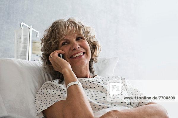 Patientin im Krankenhaus mit Handy