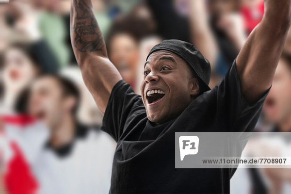 Man at sports game with arms raised