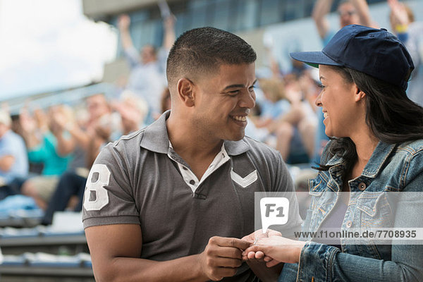 Couple getting engaged at sports game