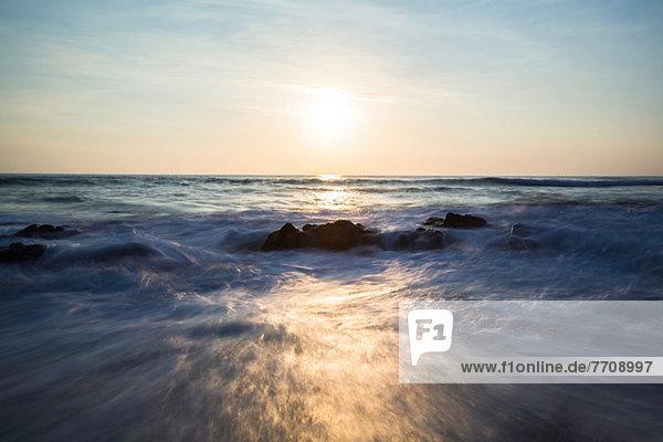 Verschwommener Blick auf die Wellen am felsigen Strand