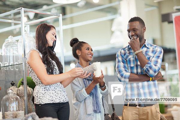 Paar-Shopping mit Verkäuferin im Geschäft