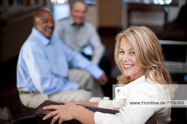 Ältere Frau lächelt im Sessel