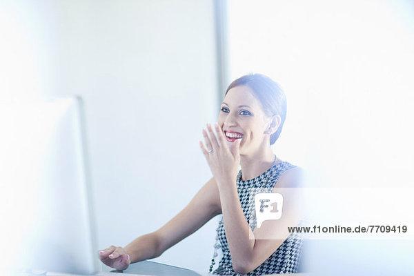 Geschäftsfrau lacht am Schreibtisch