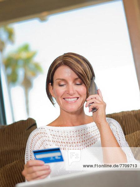 Frau beim Einkaufen am Telefon