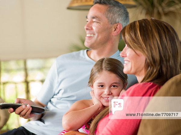 Familie entspannt gemeinsam auf dem Sofa