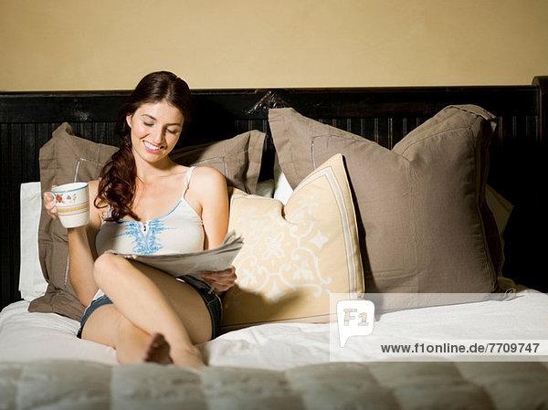 Frau liest Zeitung im Bett