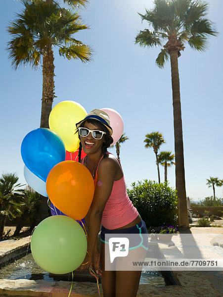 Woman holding bunch of balloons outdoors