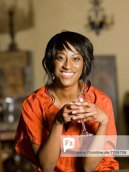 Woman having glass of wine indoors