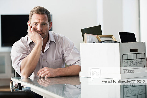 Geschäftsmann packt Kiste im Büro ein