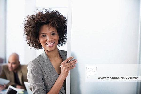 Geschäftsfrau lächelt in der Bürotür