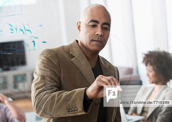 Geschäftsmann beim Zeichnen von Graphen im Meeting