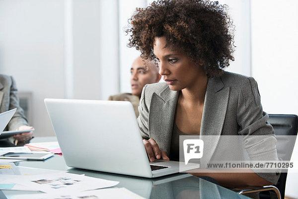 Geschäftsfrau mit Laptop im Meeting