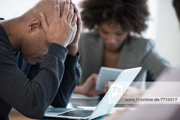 Frustrierter Geschäftsmann mit Laptop