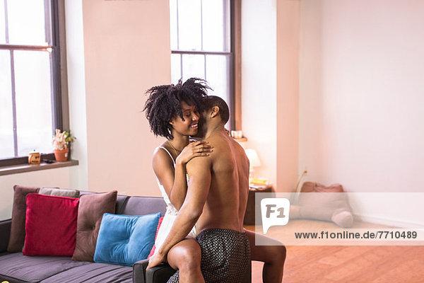 Paar Küssen auf Sofa im Wohnzimmer