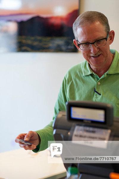 Kassiererin mit Kreditkarte im Geschäft