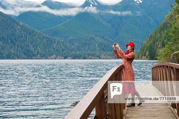 Frau fotografiert auf Holzbrücke