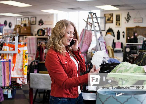 Woman on cell phone in thrift store